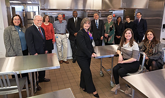 COOKING UP A NEW DIRECTION Reardon (foreground, c.) in FLP's new Culinary Literacy Center mixes up ideas with her executive staff (standing, l.–r.): Chris Caputo, Joseph McPeak, Lynn Williamson, Joe Benford, Dave Edwards, Donald Root, Sandra Horrocks, Indira Scott, and Sara Moran; Rosenbach Museum director Derick Dreher; and (seated, l.–r.) Elizabeth Fitzgerald and Melissa Greenberg. Photo ©2015 Jon Roemer