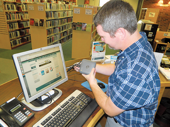 SCLS's Richard Loomis installs a Chromebox in the Bridgewater Library. Photo by Kevin Henegan