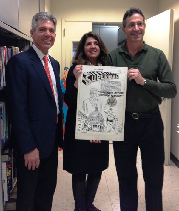 "Pictured from left: Al Plastino Jr. and MaryAnn Plastino-Charles holding the splash page of the original Superman art from ""Superman's Mission for President Kennedy"" with Jay Kogan from DC Entertainment."
