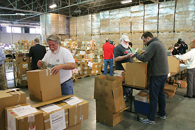 """ONE HUNDRED"" HELPERS Volunteers from the Metro United Way, Friends of the Library, and UPS, along with library staff, boxed up more than 40,000 books for delivery to every K–3 classroom in Jefferson County Public and Archdiocese schools in conjunction with the library's Share 100 Stories Before 4th Grade program. Photo courtesy of Louisville Free Public Library"