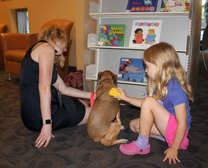 Petting and brushing one of the two therapy dogs at ICPL's Autism Accessible Browsing Hour